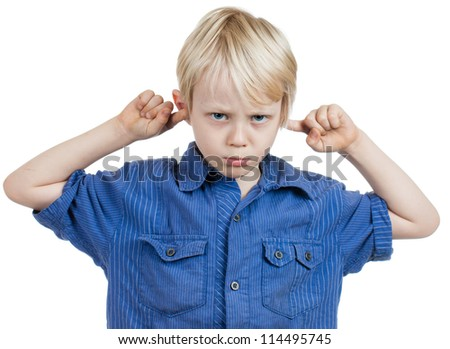 A grumpy cute young boy covers his ears with his fingers. Isolated on white. - stock photo