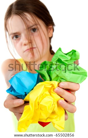 A grumpy looking primary aged girl holding some colourful scrunched up paper close to the camera.  Differential focus on the paper.