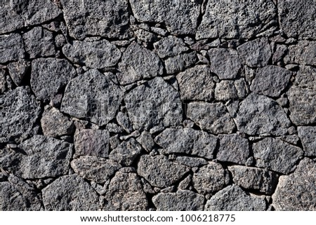 A grunge background made of a black volcanic stone wall