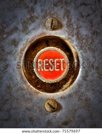 A grunge image of a reset button from the control area for an old elevator lift. - stock photo