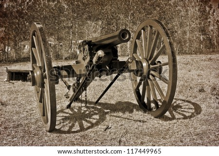 A grunge-paper textured and high contrast vintage representation of an early civil war era cannon stands ready in a meadow. - stock photo