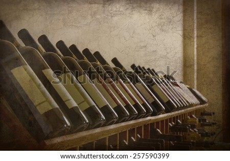 A grunge textured photo of several bottles of wine on a wine rack. Perfect display of different varieties.  - stock photo