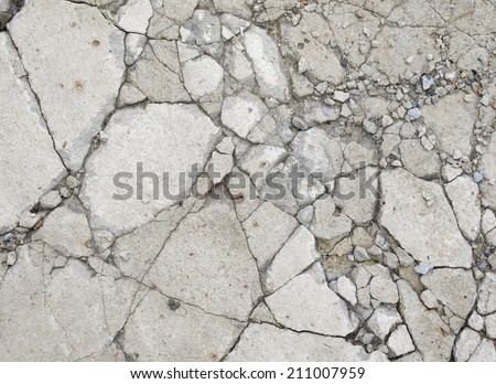A grungy fractured concrete pavement for textural background - stock photo