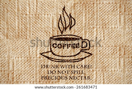 """A grungy paper napkin with a coffee cup imprint and a fun quote: """"Drink with care! Do not spill, precious nectar."""".  - stock photo"""