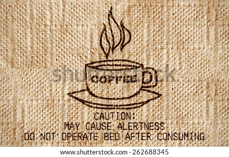 """A grungy paper napkin with a coffee cup imprint and a funny quote: """"Caution: May cause alertness. Do not operate bed after consuming"""".  - stock photo"""