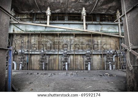 A grungy scene at an abandoned factory hall, rust and paint peeling from the walls creating a magnificent view. - stock photo