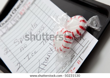 A guest check on a black tray with red and white mints - stock photo