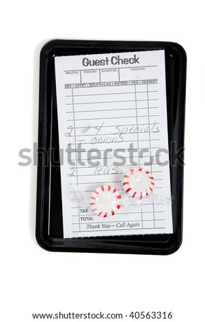 A guest check on a tip tray with mints on a white background - stock photo
