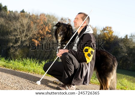 A guide dog takes care of his blind master - stock photo