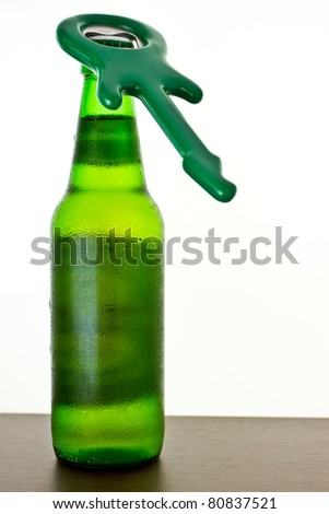 A  guitar opener on the bottle of beer on isolated white - stock photo