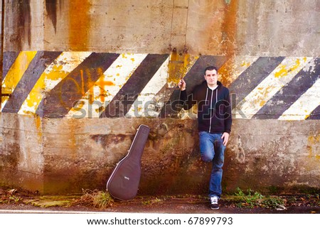 A guitar player stands outside while modeling himself and his guitar for a music promo photo shoot. - stock photo