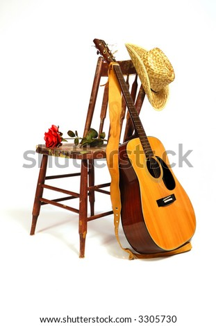 A guitar rests against a wooden chair that is splattered with paint. - stock photo