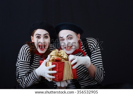 a guy and a girl in clown suits holding a box with a gift