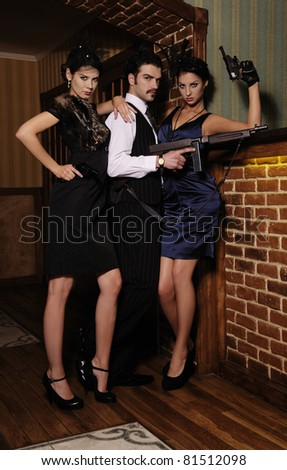 A guy and two beautiful young women in the image of gangsters with guns. - stock photo
