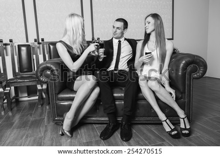 A guy and two girls in the room, tense. Group young people drink wine and enjoy the evening. Human feelings - jealousy, love, passion, betrayal. - stock photo