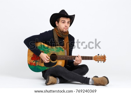 A guy in a hat is playing on a guitar sitting on the floor with a surprised look. Isolated.