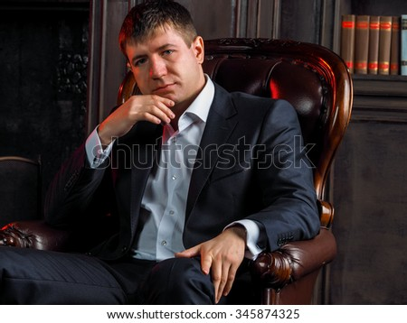 A guy in a suit sitting in an armchair in the old English room near the fireplace and bookcase - stock photo