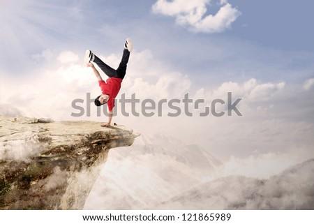 A guy is doing cartwheel acrobatic on mountain high - stock photo