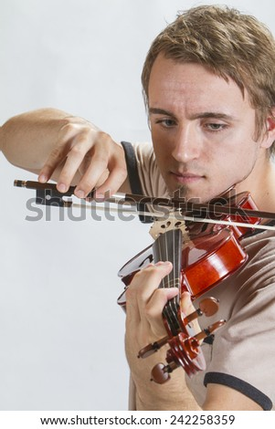 A guy playing a violin. - stock photo