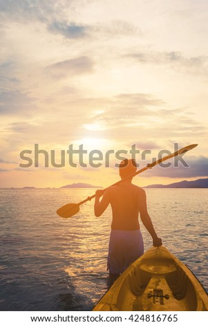 a guy pulling kayak to the sea in sunset, vacation holiday summertime concepts, vintage tone - stock photo