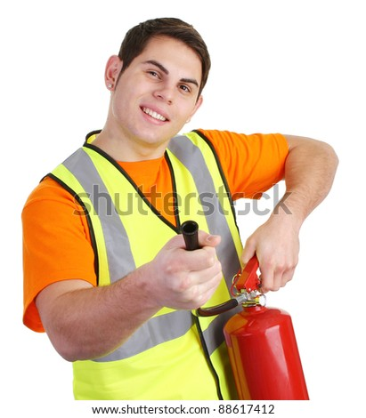 A guy wearing a hiviz jacket and holding a fire extinguisher - stock photo