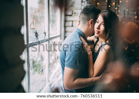 A guy with a girl is celebrating Christmas. A loving couple enjoy each other on New Year's Eve. New Year's love story.