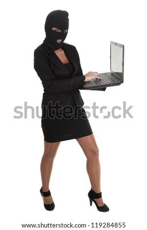 a hacker, committing a crime  through laptop - stock photo