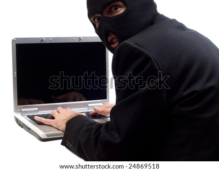 A hacker is using a laptop computer to steal information, isolated against a white background - stock photo