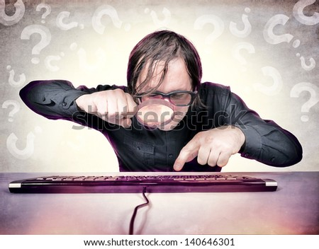 A hacker with a magnifying glass looking for something on the keyboard - stock photo