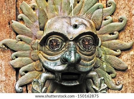 """A hagoday or door knocker is also supposedly in medieval folklore a replica of the beast.  Here the beast begins to see after someone knocks on the door.  The question:  """"What waits behind the door?' - stock photo"""