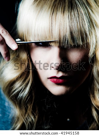 A hair stylist cutting her own hair, portrait. - stock photo