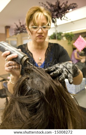 A hairdresser applying hair color to a clients head.  Shallow depth of field with focus on the hair. - stock photo