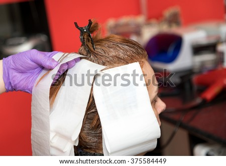 A hairdresser coloring hair of a woman. Selective focus. - stock photo