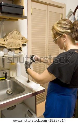 A hairdresser mixing a hair color formula in the back room. - stock photo