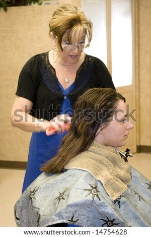 A hairdresser working on a client in the salon.