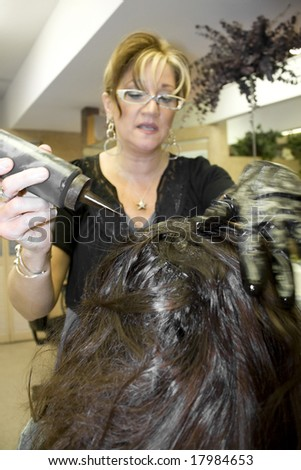 A hairdresser working on a clients hair color at the salon - stock photo