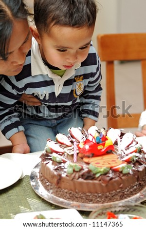 A half-asian boy and his asian mother blow candles on a birthday cake