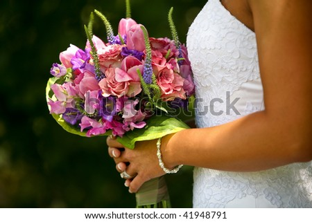 A half-body view of a bride holding up a bouquet