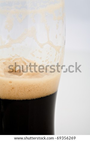 A half drained pint of stout beer - stock photo