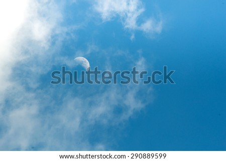 A  half moon in noon and beautiful blue sky and white clouds in good weather and summer day. Photo for background. - stock photo