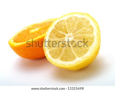 A half of fresh orange and a lemon one on a white table - stock photo