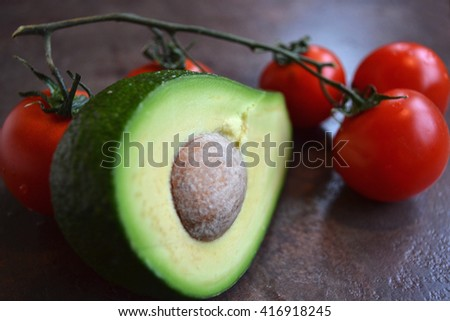 A half of ripe juicy avocado and red tomatoes branch are on the shiny stone kitchen counter. Tasty food for beauty. - stock photo