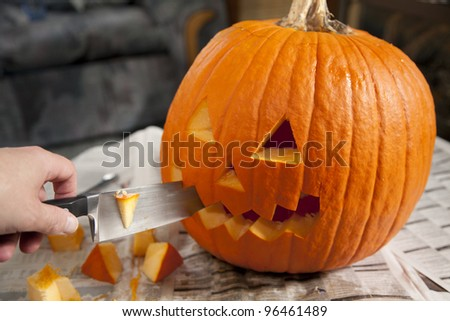 A Halloween jack o' lantern being carved for Halloween. - stock photo