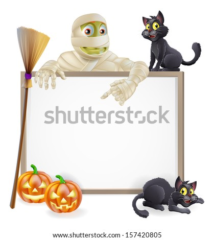 A Halloween sign with a classic mummy character pointing down and witch's black cats, broomstick and Halloween carved orange pumpkins - stock photo