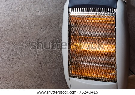 A halogen or electric heater against concrete wall