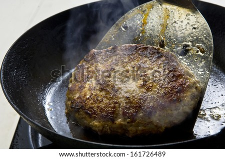 A hamburger being flipped in a frying pan. - stock photo