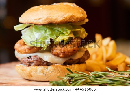 A hamburger consisting of meat patties, lettuce, cheese and French fries served on a wooden plate