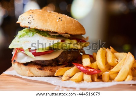 A hamburger consisting of meat patties, vegetables, cheese and French fries served on a wooden plate