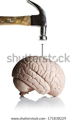 A hammer and nail with a brain model  - stock photo