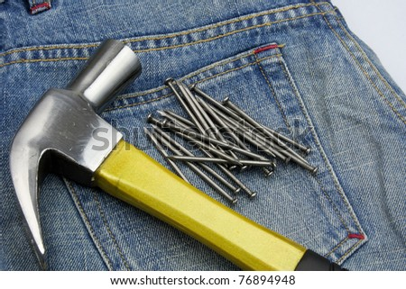 A Hammer and nails on jeans - stock photo